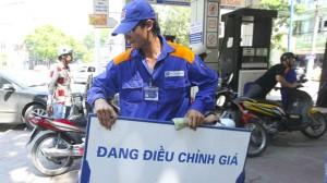 Nhân viên đang điều chỉnh giá săng dầu tại một cây săng trên TP Hà Nội